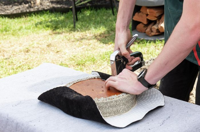 Person attaching new fabric to a bar stool seat using a staple gun