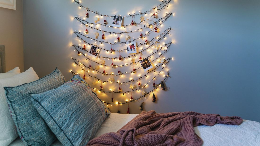 Fairy lights zig zagging down a bedroom wall with polaroid pictures and christmas decorations attached throughout it