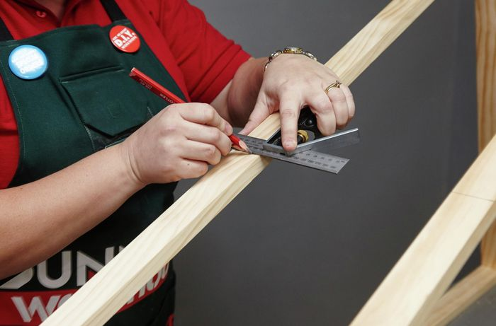 Person using metal ruler and pencil to make a mark on a length of timber.