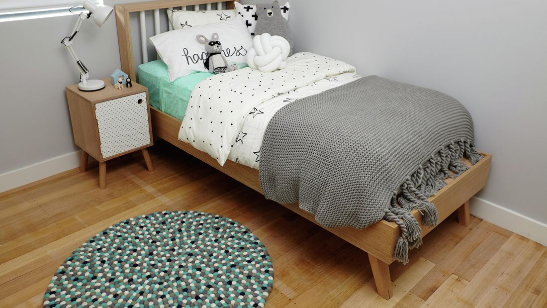 Kids bedroom with single bed and bedside table, that has toys and a lamp.