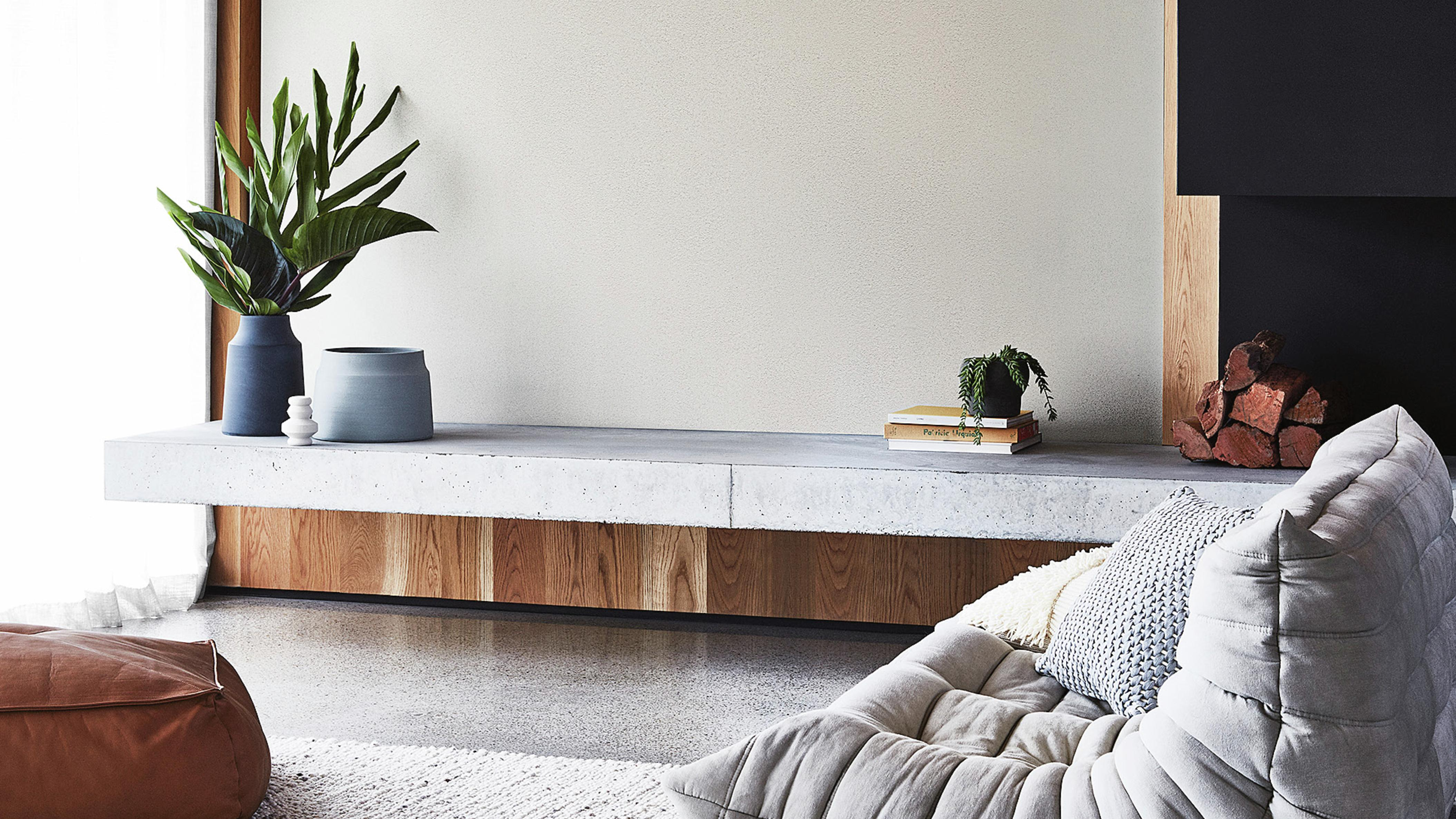 Modern living room area with stone entertainment unit with plants and other decor on top.