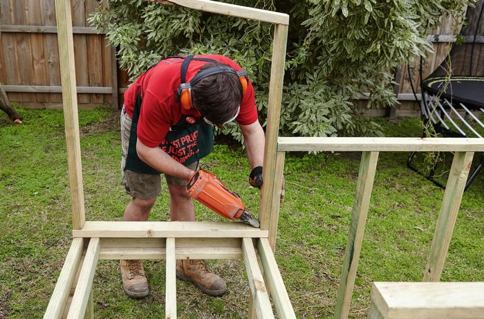 A wooden frame for a chicken coop being nailed together by a Bunnings team member with a nail gun