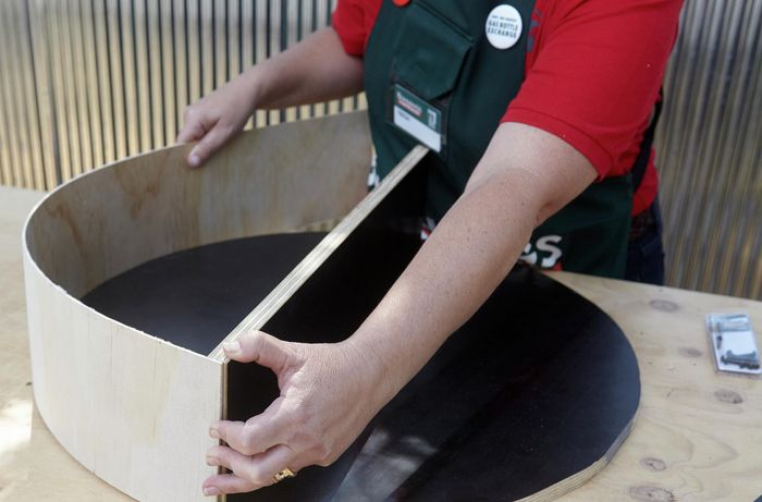 A person curving a strip of plywood around a circular plywood base with a shelf