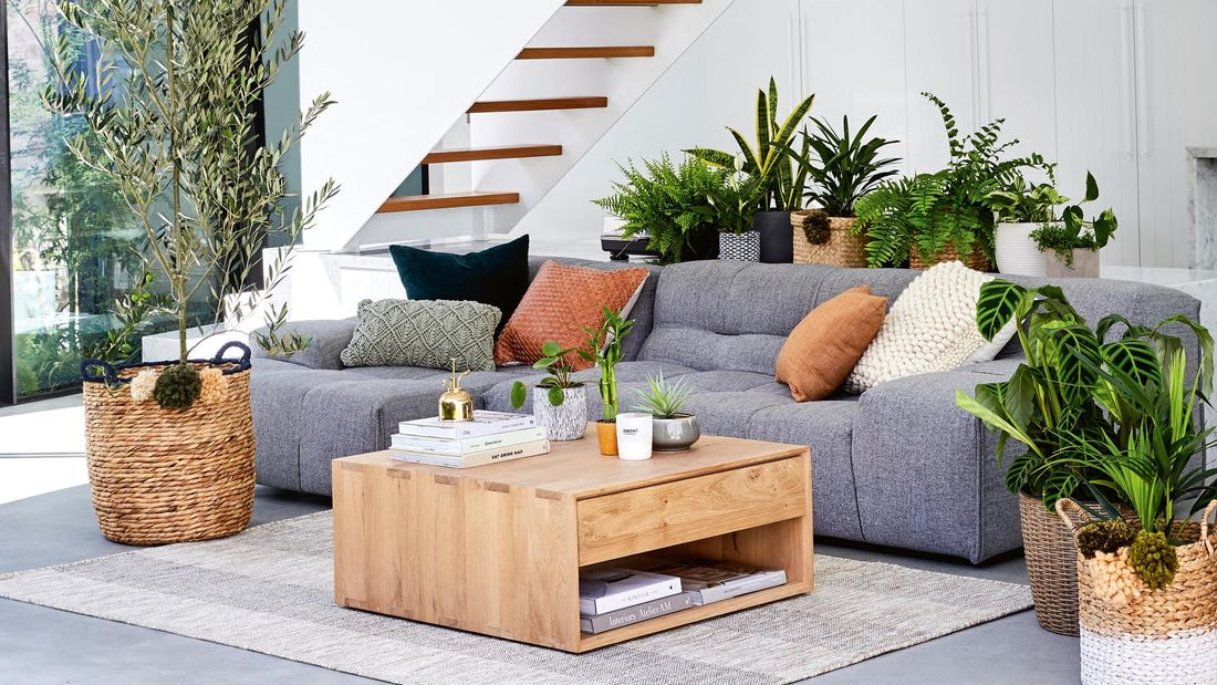 Modern living area with grey sofa, white walls and staircase opening onto grassed area