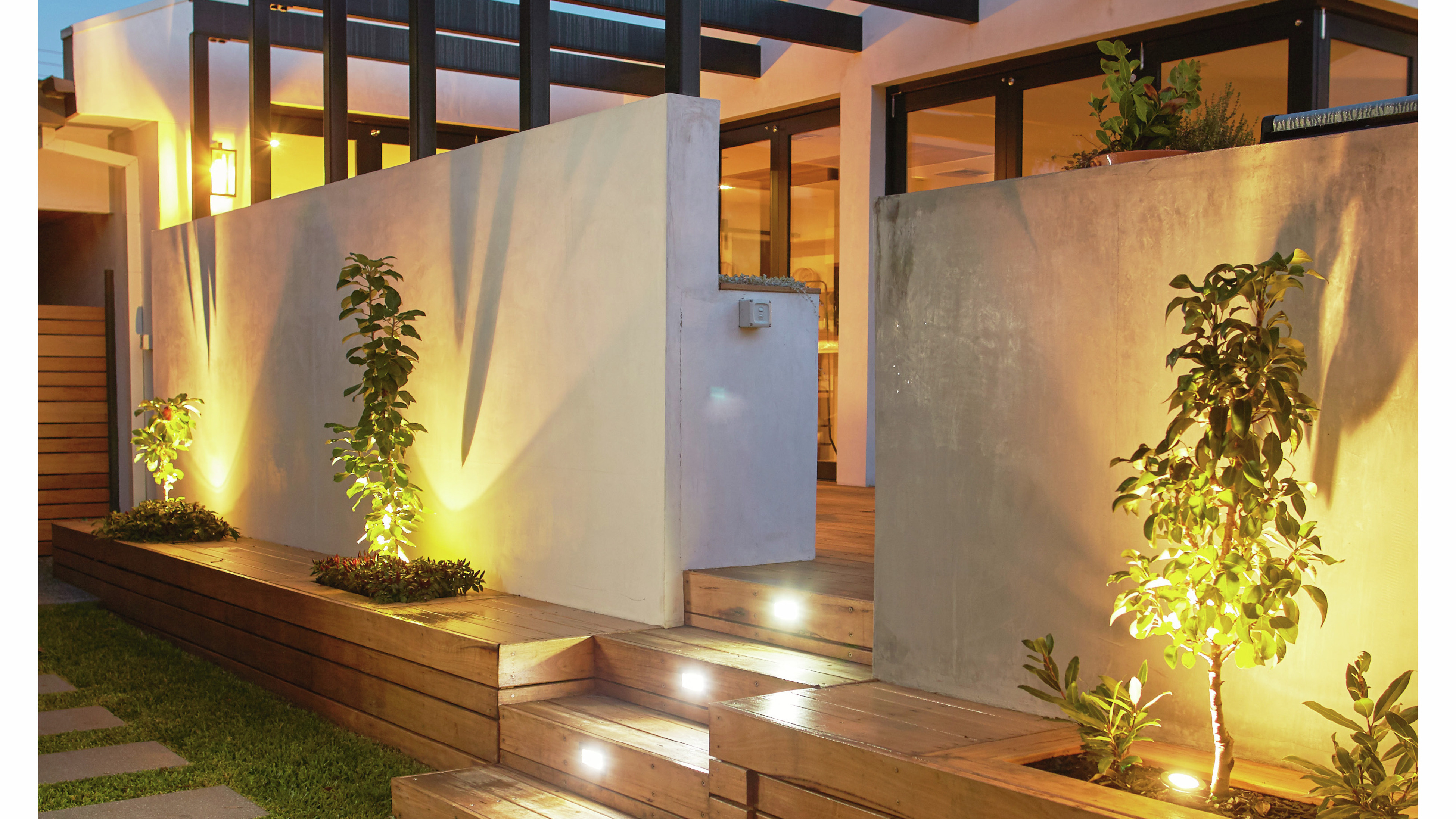 Modern house with decking and soft lighting at night time.