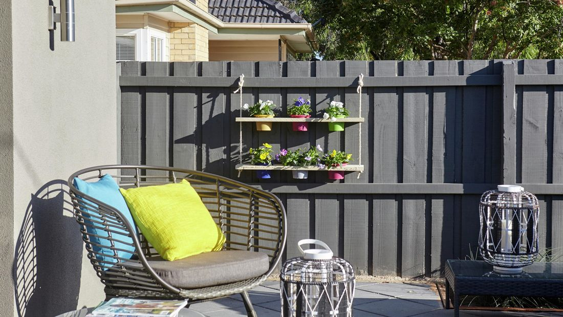 A pot plant holder with six pots hanging on a paling fence