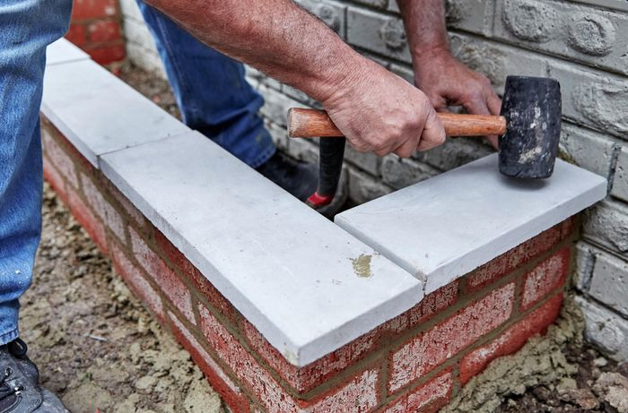 A person using a mallet to tap concrete capping blocks into position