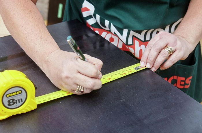 A person marking a measurement onto formply
