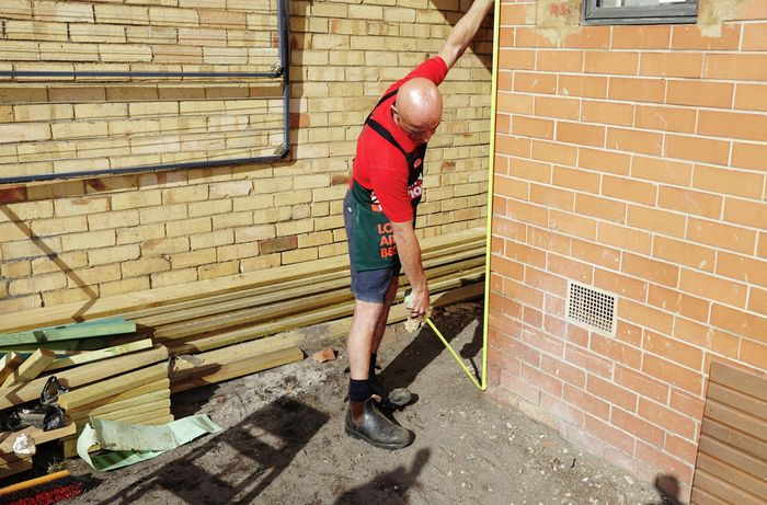 A person measuring the height of a brick wall at the corner
