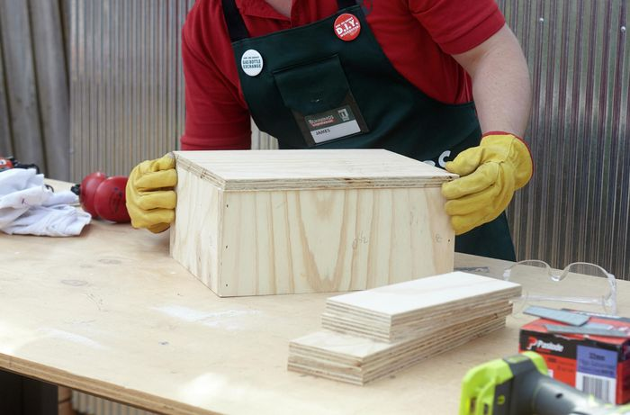 Person lining up pieces of timber to glue and then nail together