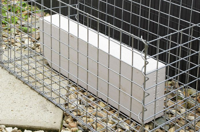 A concrete block sitting inside an otherwise empty gabion cage