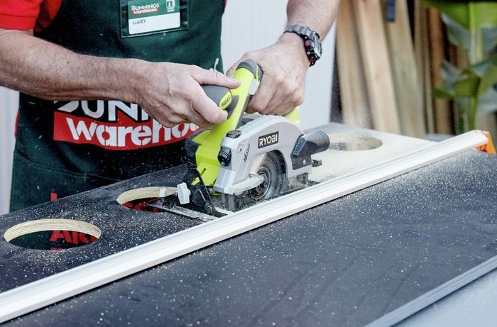 A circular saw cutting through a piece of particle board painted black with a hole in the centre