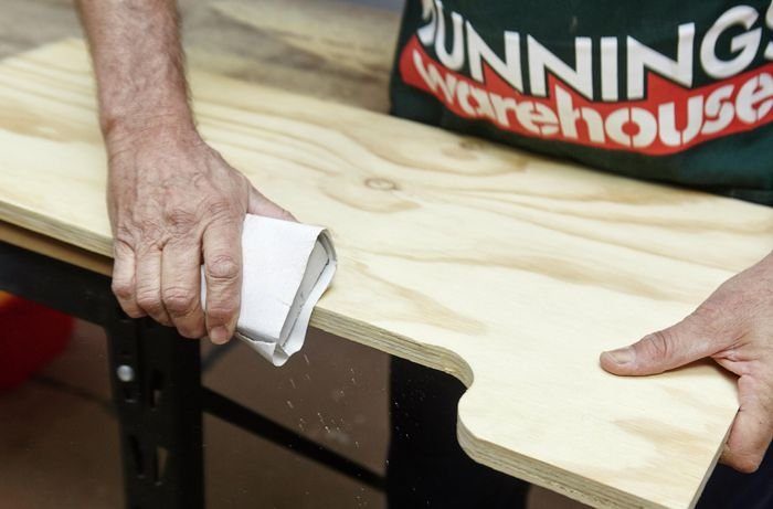 Person sanding edges of ply panel