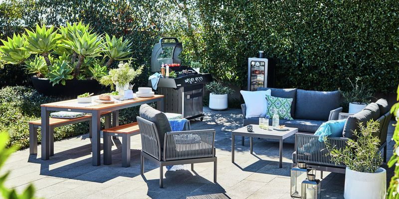 An outdoor entertaining area with table and chairs, couch and barbecue.