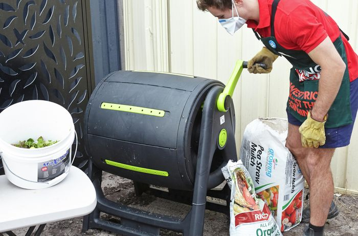 A tumbling barrel being turned to blend its contents together by a Bunnings team member