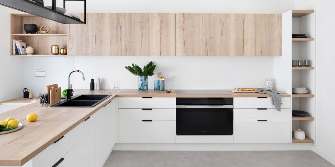 Modern family kitchen with light wooden cabinetry and benchtops