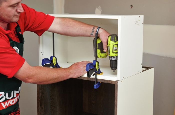 A person attaching two cabinet units using a clamp and cordless driver