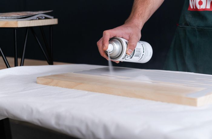 Bunnings team member spray painting timber