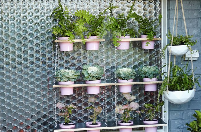 A completed vertical garden with three tiers, each tier holding four pink plant pots, in front of a circular patterned glass window pane