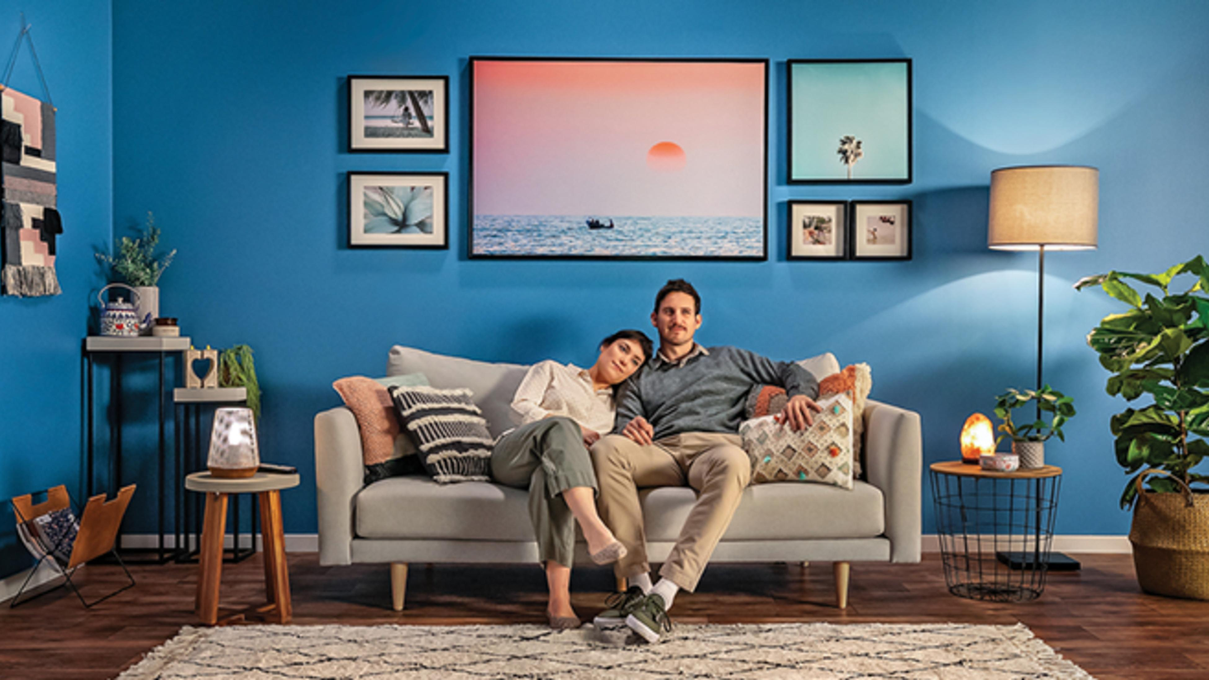 A couple sitting on a couch in a living room with blue walls, picture frames on the wall, lamps and indoor plants.