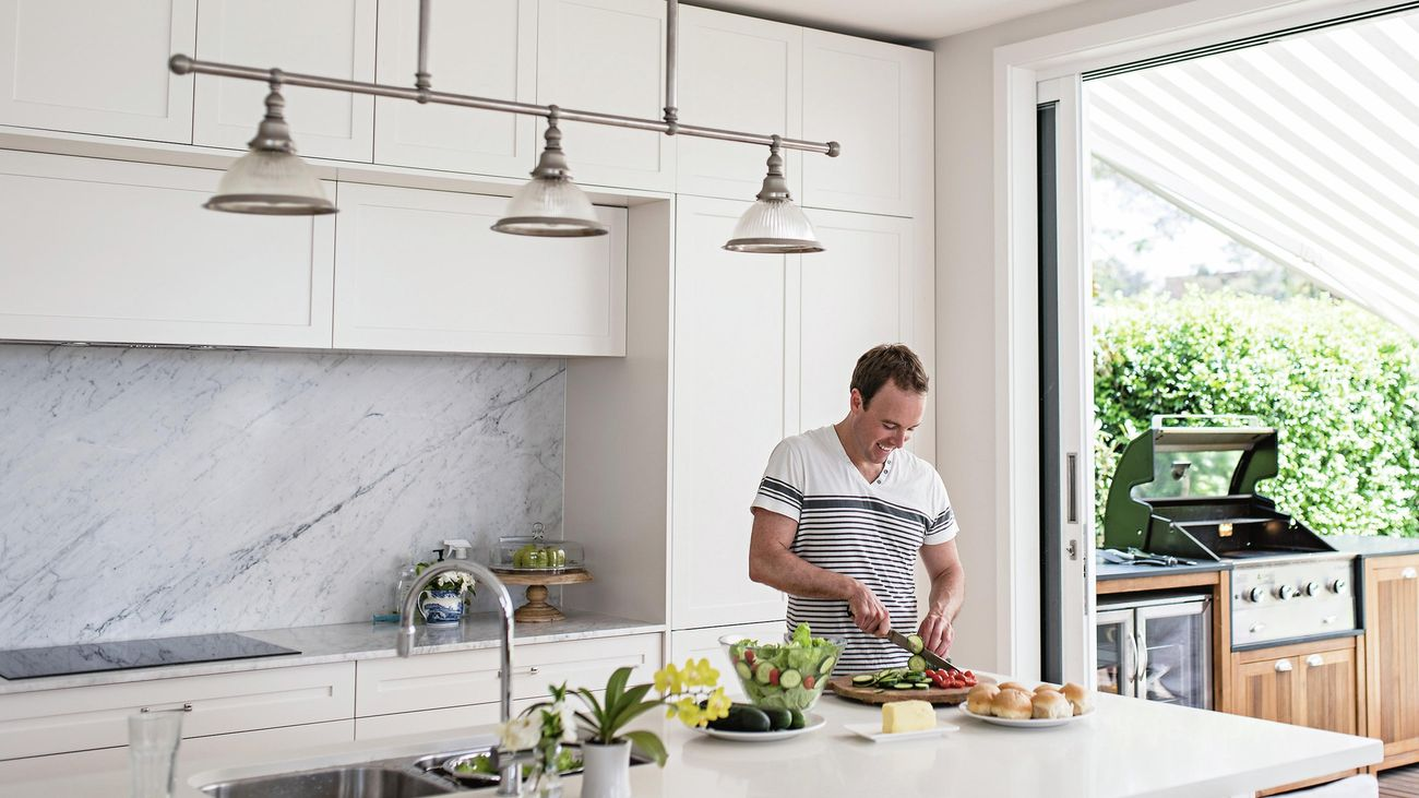 Man chops up a cucumber for a leafy green salad in a modern kitchen.