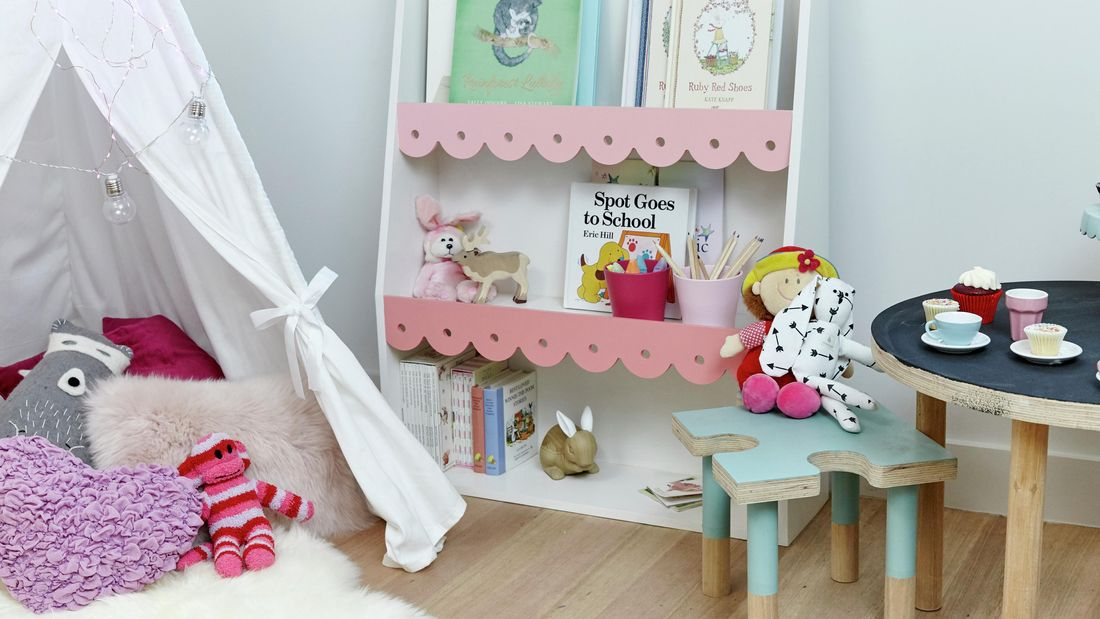 A decorated bookshelf painted pink and white in a child's bedroom