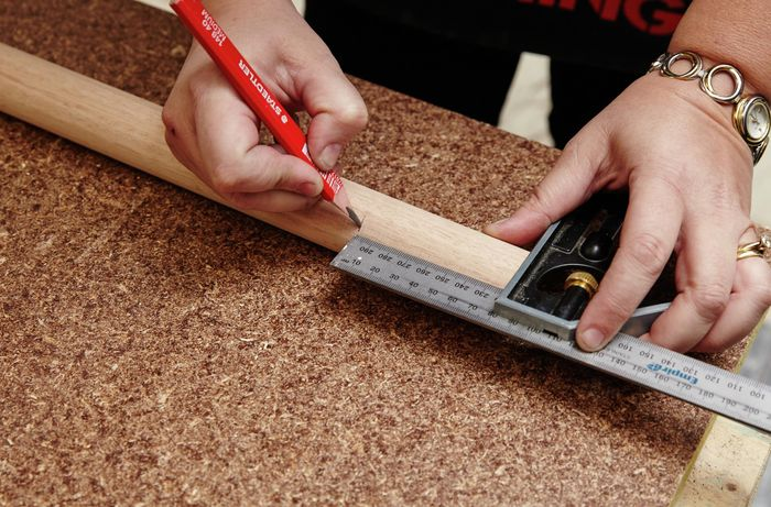 A square rule and pencil being used to mark a piece of timber for cutting