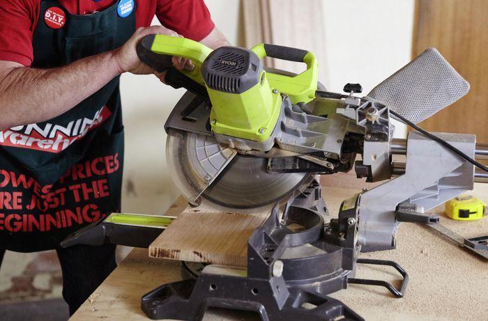 A Bunnings team member using a circular saw to cut timber