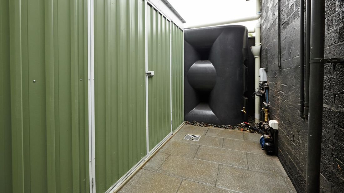 An outdoor area with a large, green steel shed and a black rainwater tank