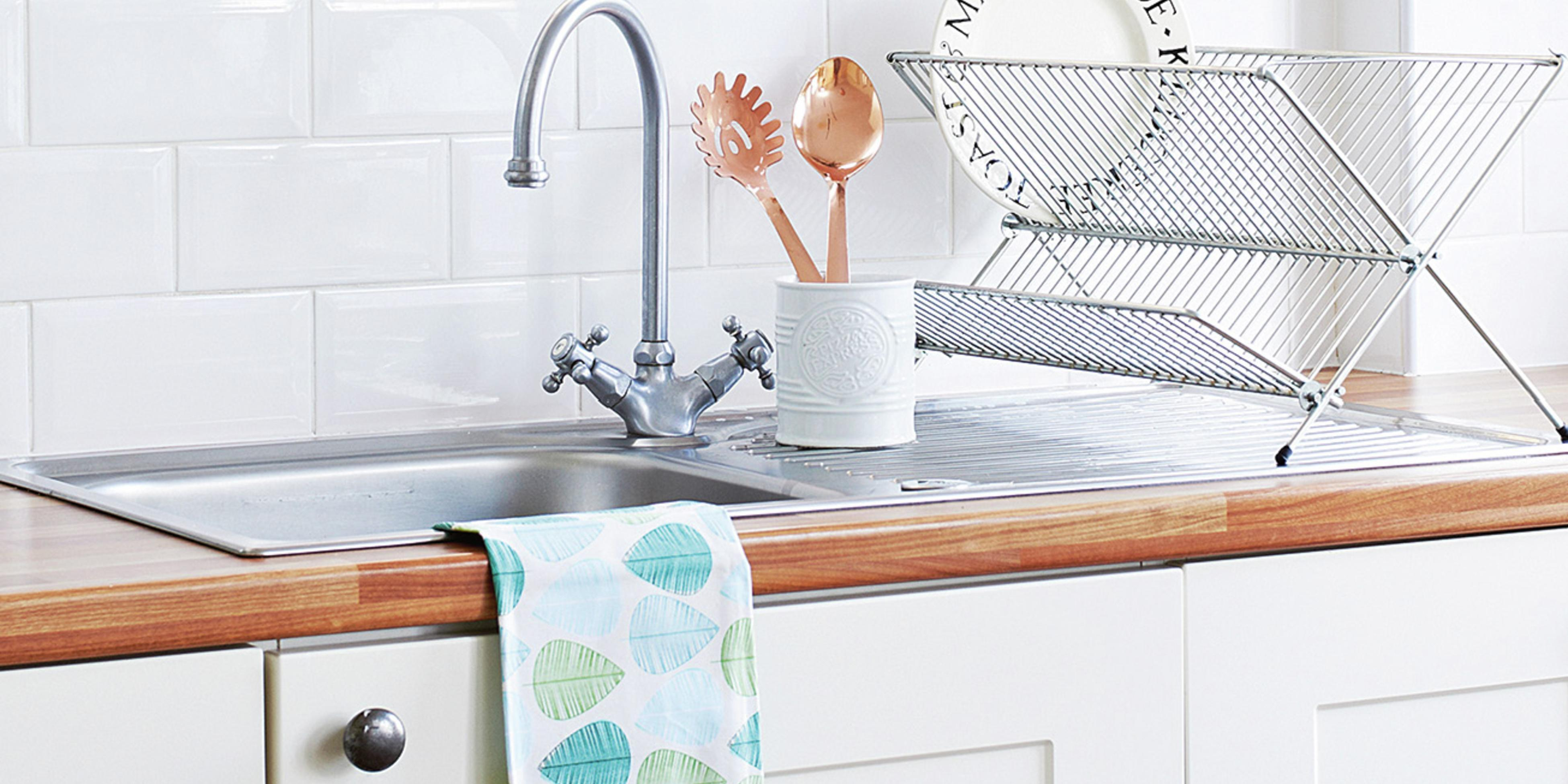 Kitchen timber benchtop with over-mounted stainless steel sink and a drying rack