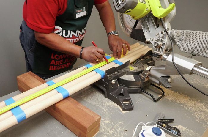 Lengths of dowel being marked for cutting bar stool legs