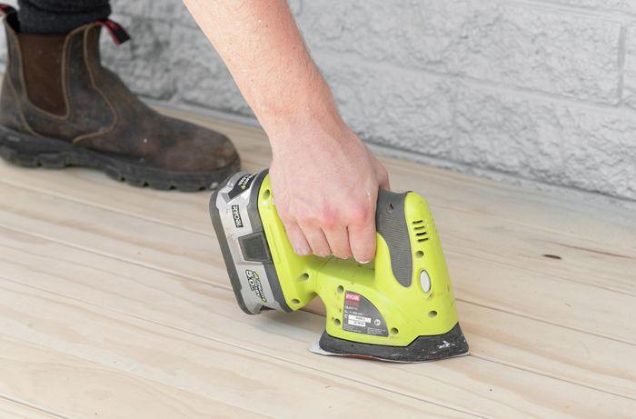 Person sanding a deck.