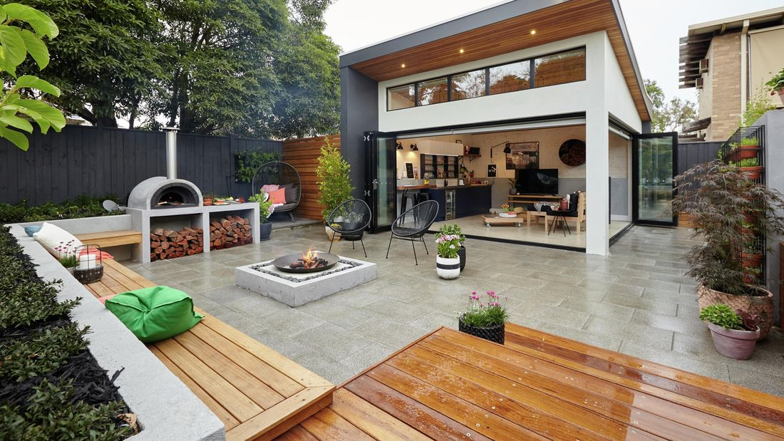 An outdoor entertaining area with firepit, designer chairs with throw cushions, pizza oven and firewood pile, decking and benches and an enclosed lounge area with TV, couches and wheeled pallet coffee table