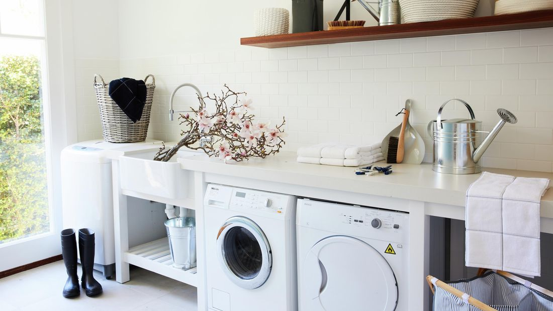 Laundry with washing machine, dryer, watering can and gumboots