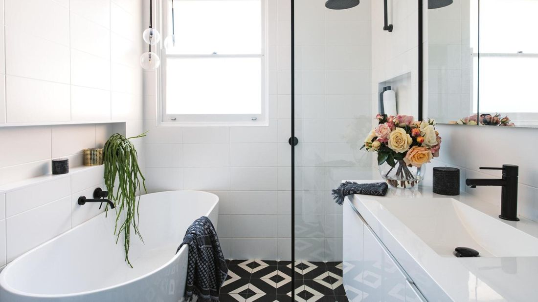 Modern bathroom with glass shower, porcelain white bath and vanity and a vase of roses.