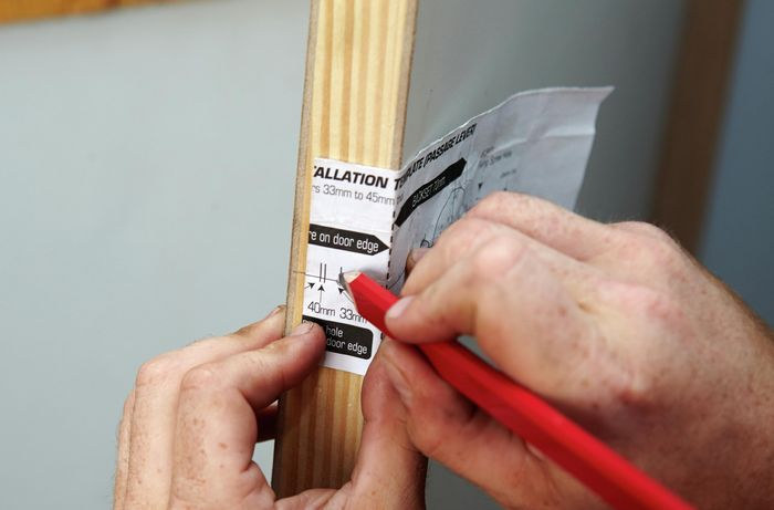 Using the marker guide provided with the doorhandle to mark the drilling position