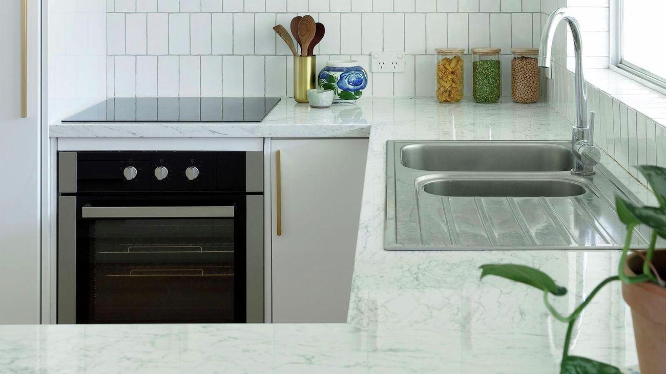 white kitchen with tiled splashback and kitchen utensils