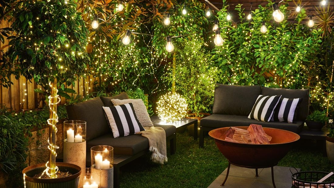 A backyard lit by fairy lights and candles, with outdoor furniture surrounding a fire pit