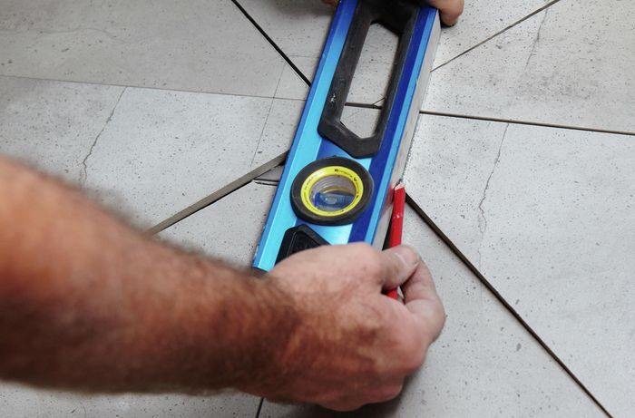 A person marking tiles using a spirit level