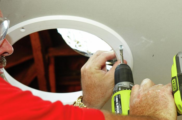 A skylight diffuser template being screwed into the ceiling by a Bunnings team member with a power drill