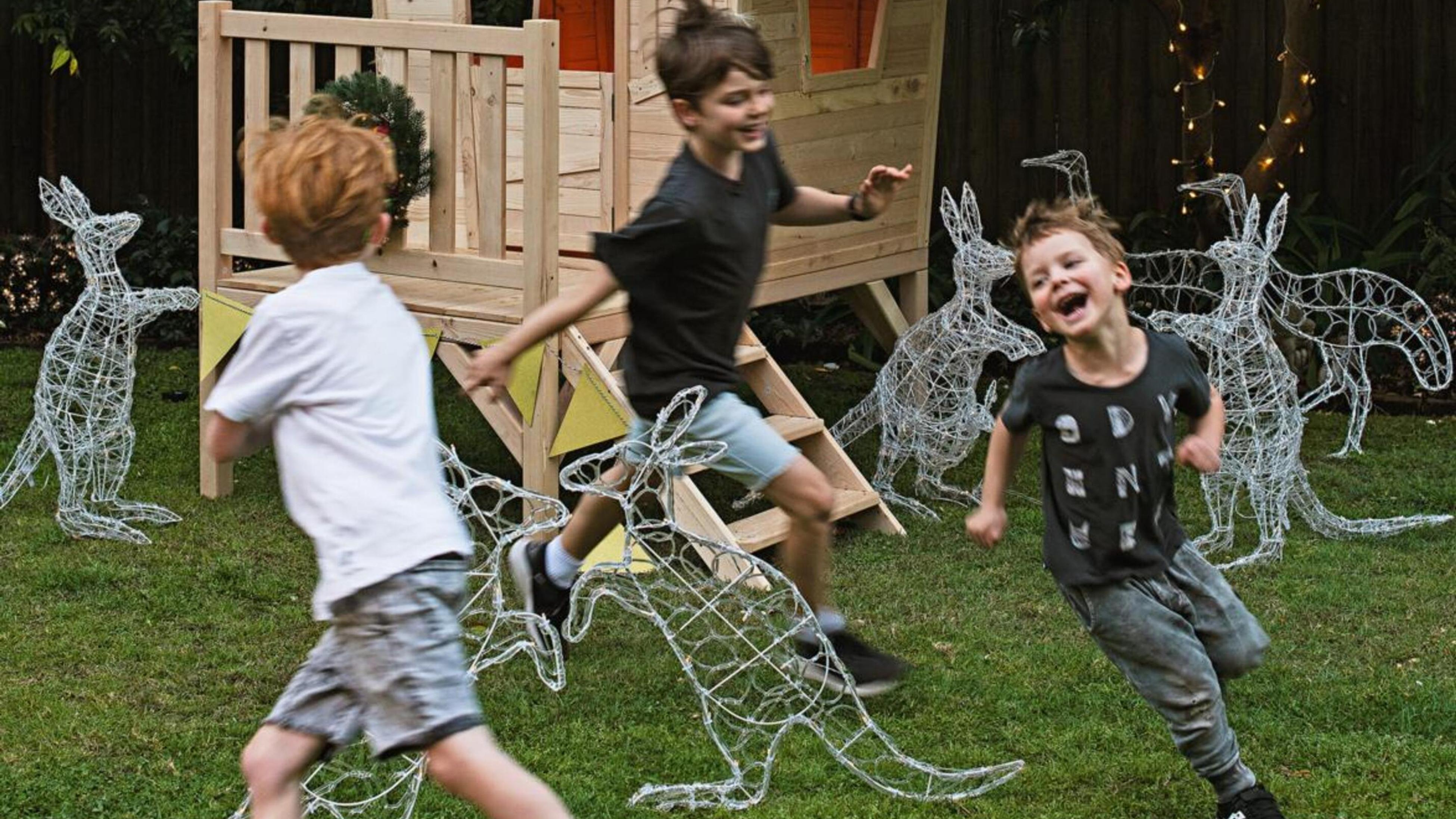 Children running around solar statues in the shape of animals.