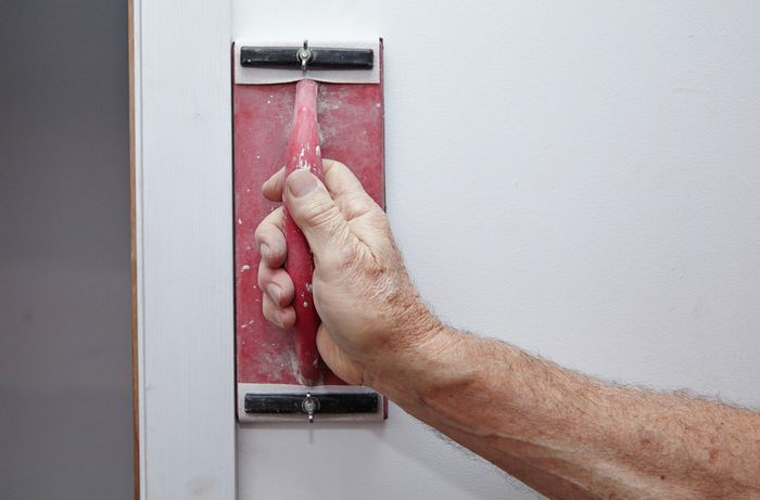 A handheld sander being used on a blank wall