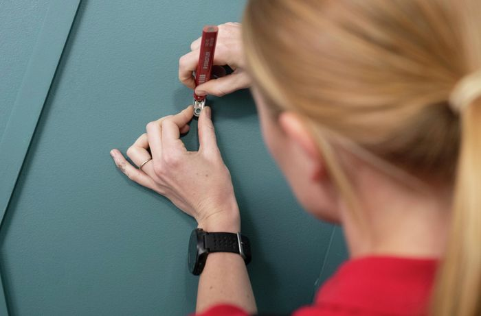 Person marking wall with pencil, to indicate where the wall hook will go.