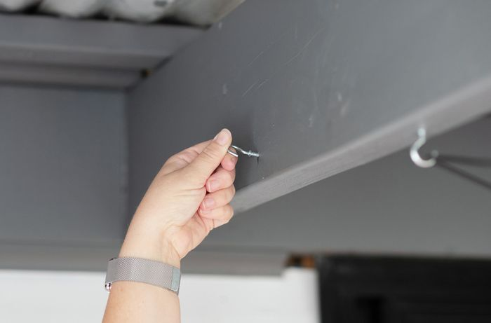A Bunnings team member securing a screw in a patio roof beam