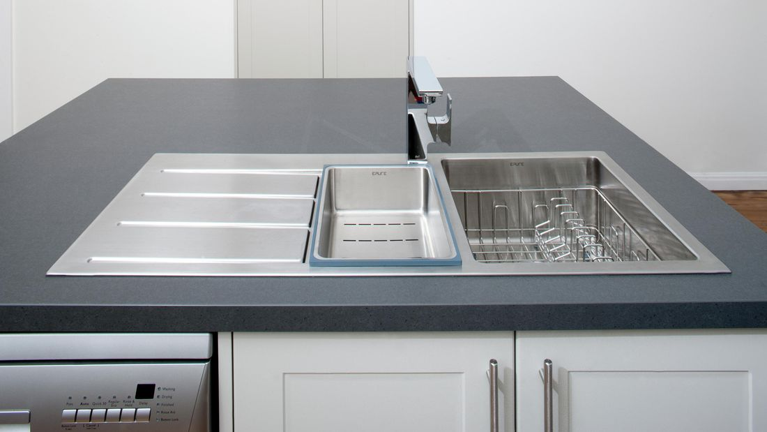A stainless steel kitchen sink built into a kitchen island complete with dishwasher