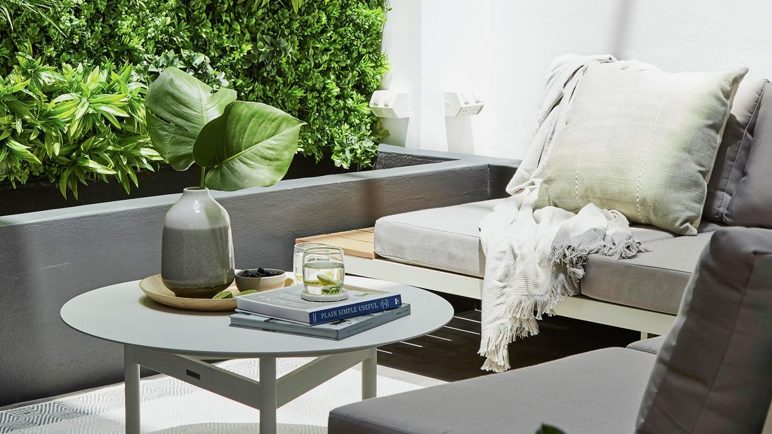 An outdoor corner sofa with coffee table sat next to a grey planter box