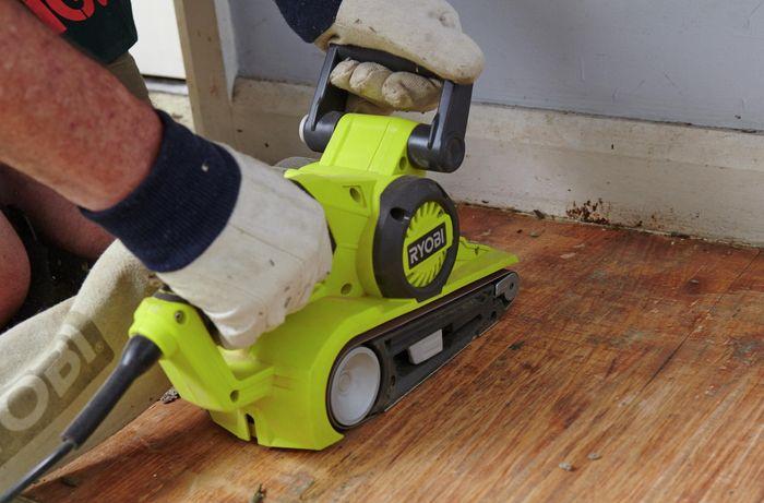 Gloved hands sanding the hardwood floors with a belt sander