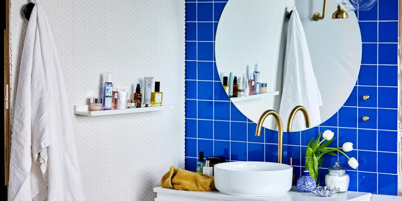 Bathroom with round mirror, brass tap and blue tiles.