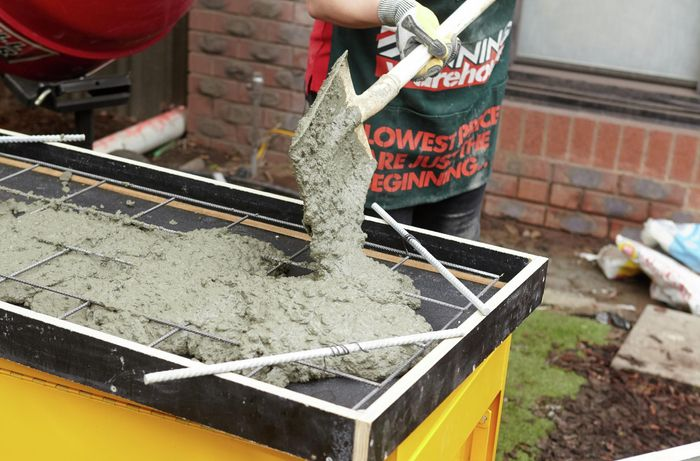 Person using shovel to scoop concrete into form ply frame with reinforcing mesh.