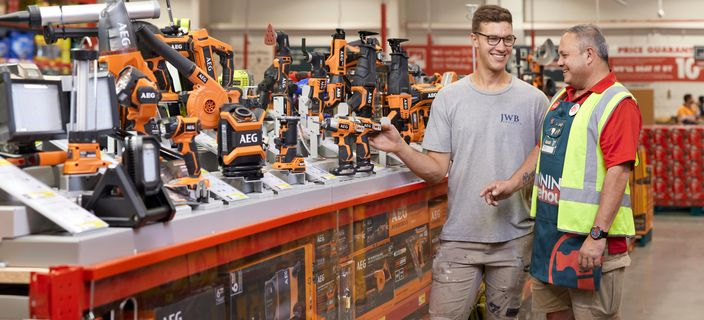 Bunnings team member helping customer pick out tools.